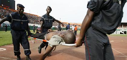 Rettungskräfte tragen einen verletzten Mann: 22 Menschen wurden bei einer Massenpanik im Houphouet-Boigny-Stadion getötet, mehr als 130 verletzt