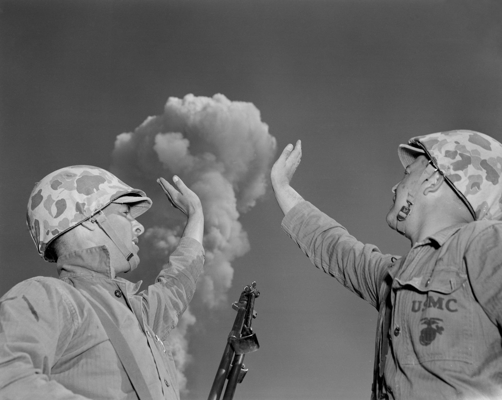 Soldiers pose below an atomic cloud at the Nevada Proving Ground. Soldiers conducted maneuvers in the vicinity of nucle