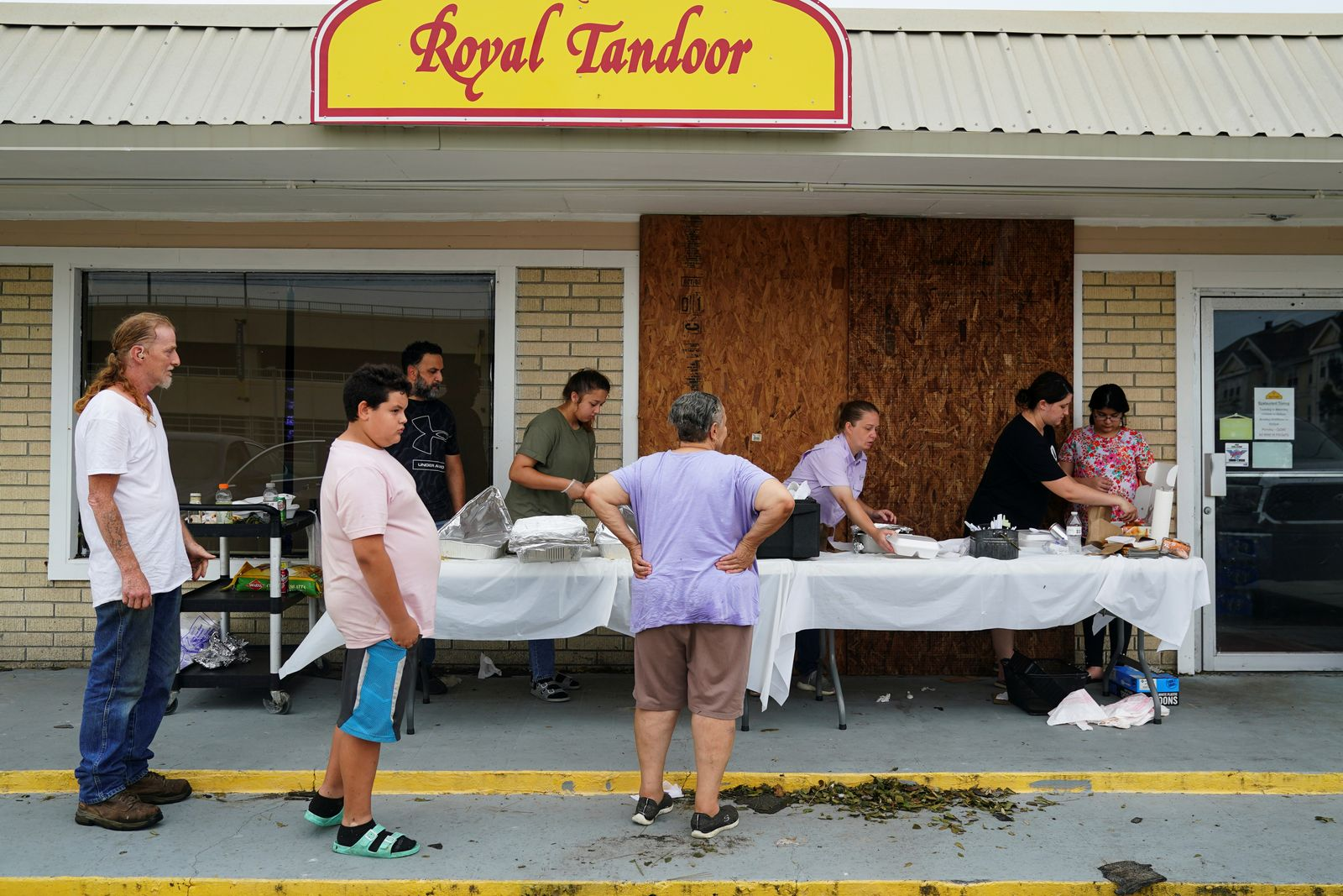 Amanda Abassi serves free hot food to community members with her daughter and extended family in front of her restaurant Royal Tandoor after Hurricane Laura passed through the area in Lake Charles