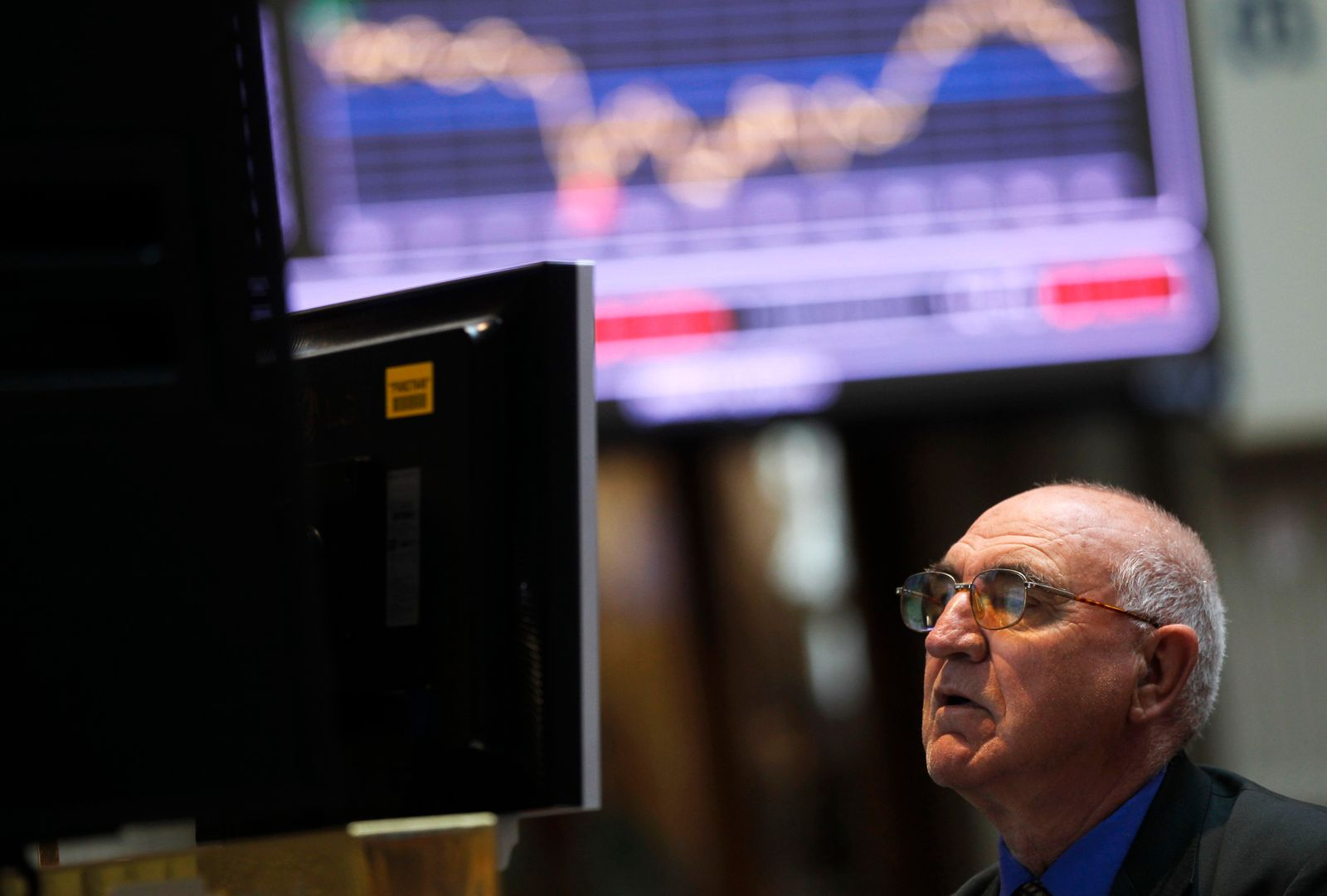 A trader looks at screens during trading at the Madrid bourse
