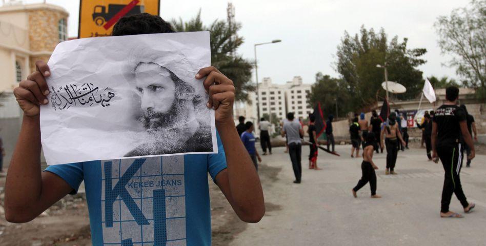 Demonstrant mit Foto des Geistlichen Nimr al-Nimr in Manama, Bahrain: Diplomatische Verbindungen zu Teheran gekappt