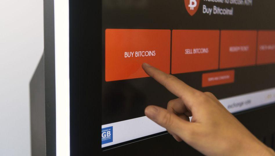 Eine Person kauft an einem Bitcoin-Automaten in Zürich Bitcoin