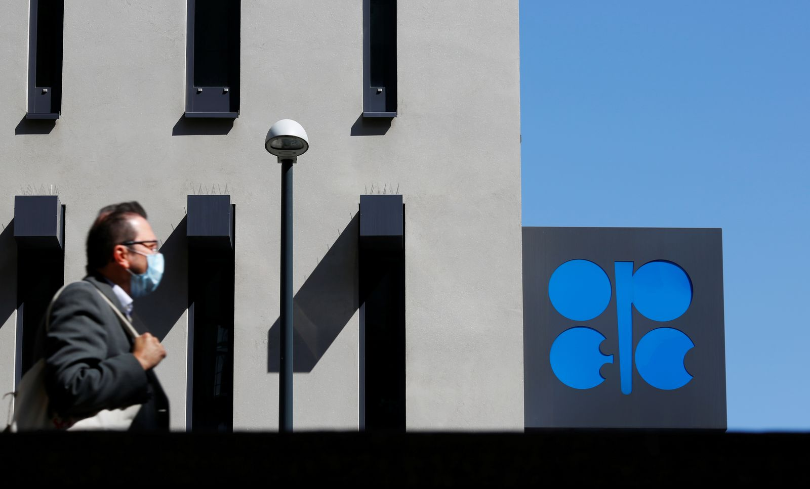 A person passes the OPEC logo in front of its headquarters in Vienna