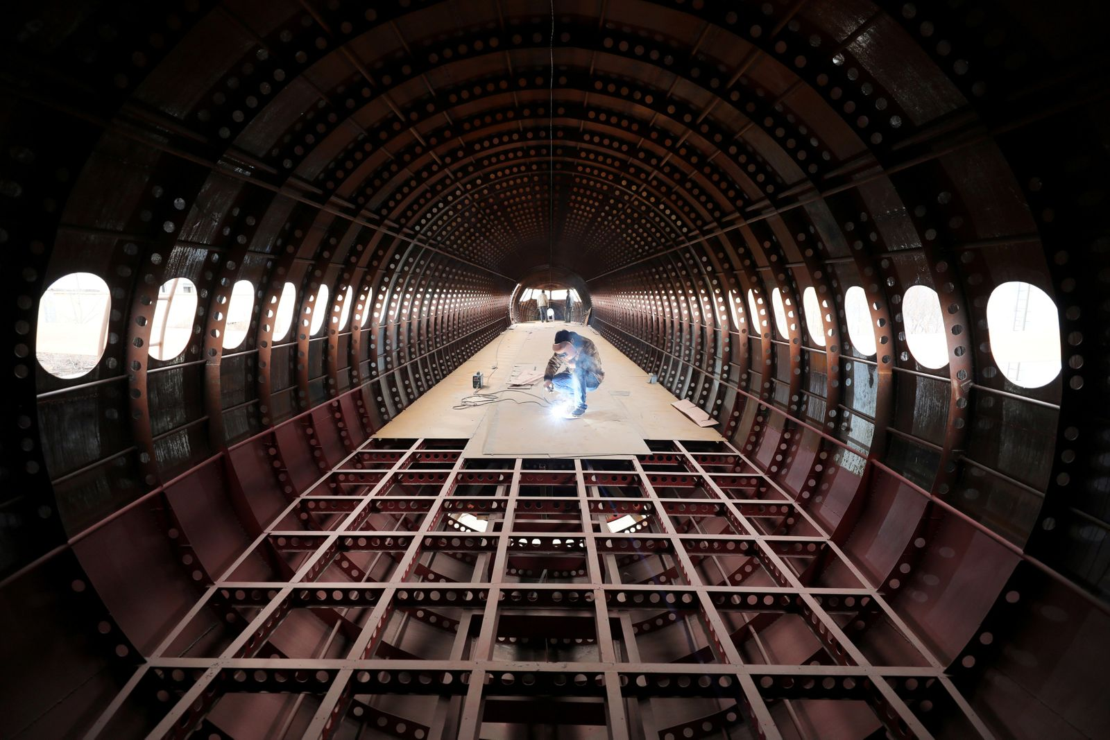 Zhu Yue welds inside a full-scale replica of Airbus A320 plane, in Kaiyuan