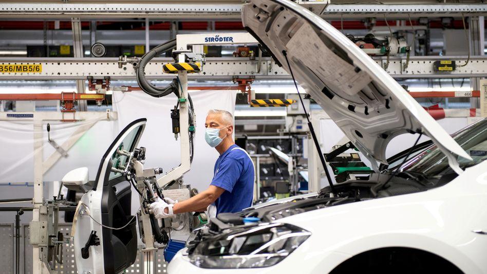 Arbeiten in der Pandemie: Ein Volkswagenmitarbeiter mit Maske