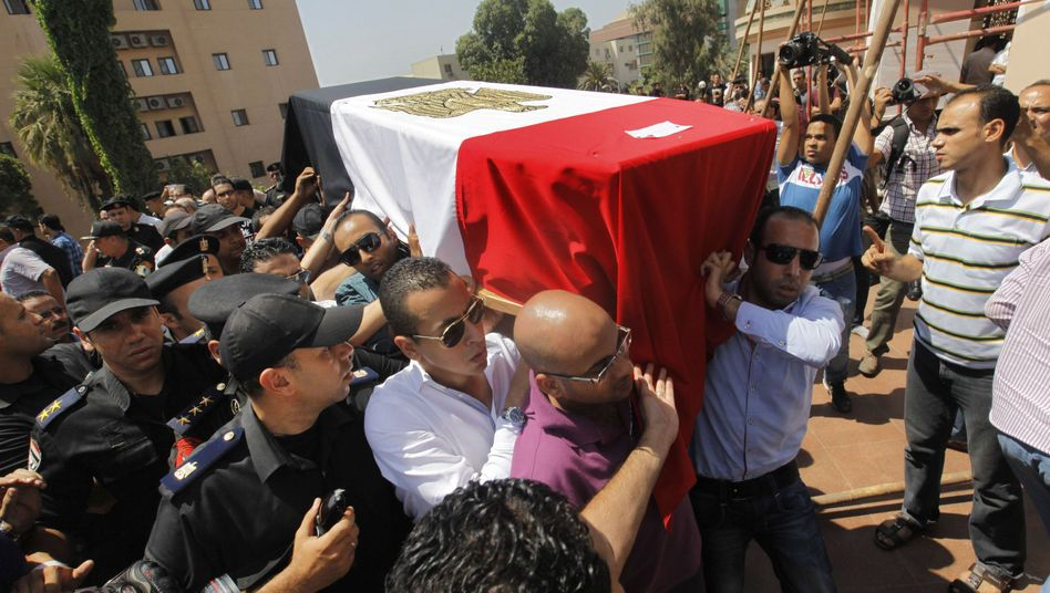 Egyptian relatives and colleagues of policemen who were killed during Wednesdays clashes carry coffins covered with national flags.