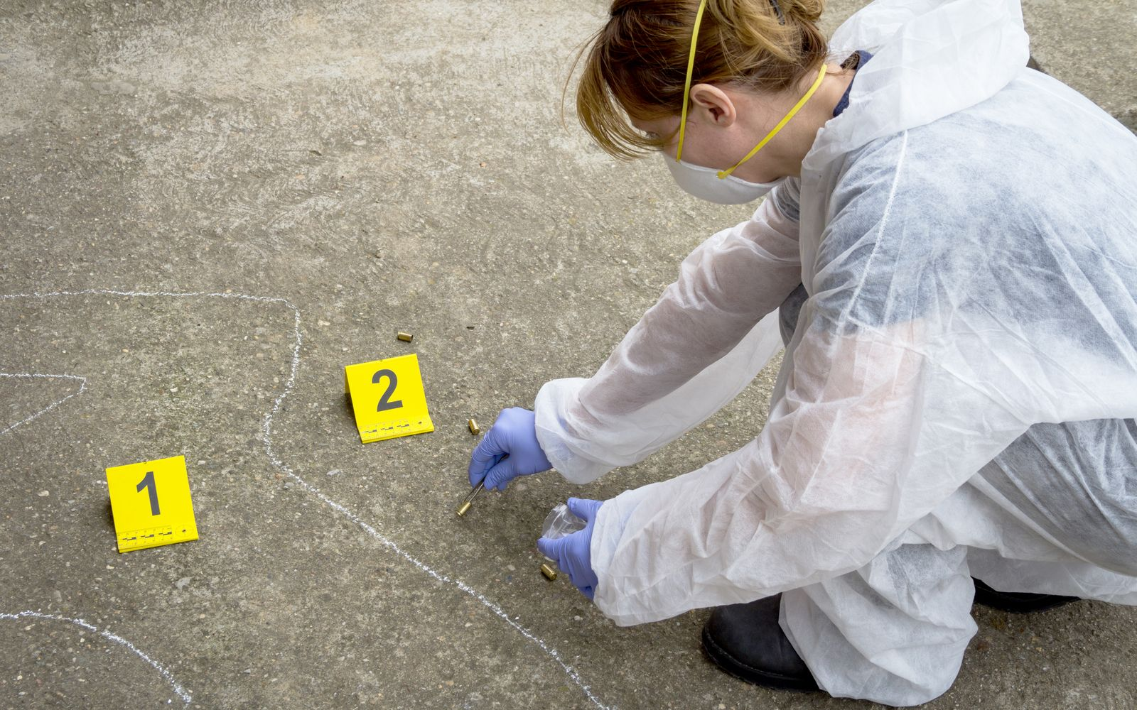 Woman forensic expert collects evidence at the crime scene