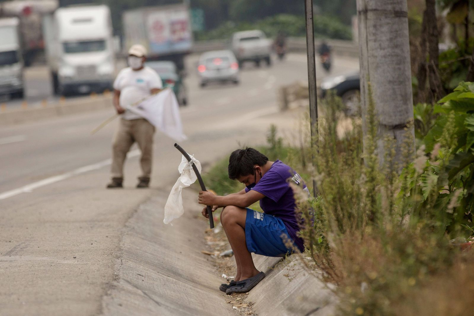 A boy waves a white flag to ask for help due to hunger, in El Tejar, Guatemala, 29 April 2020. Guatemala is on its fift