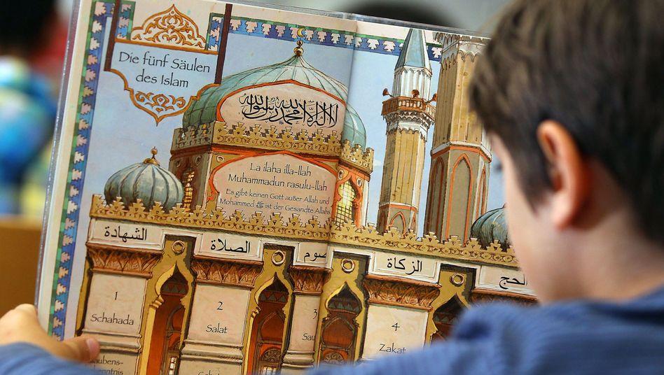 Junge liest während des islamischen Religionsunterrichts in einem Schulbuch