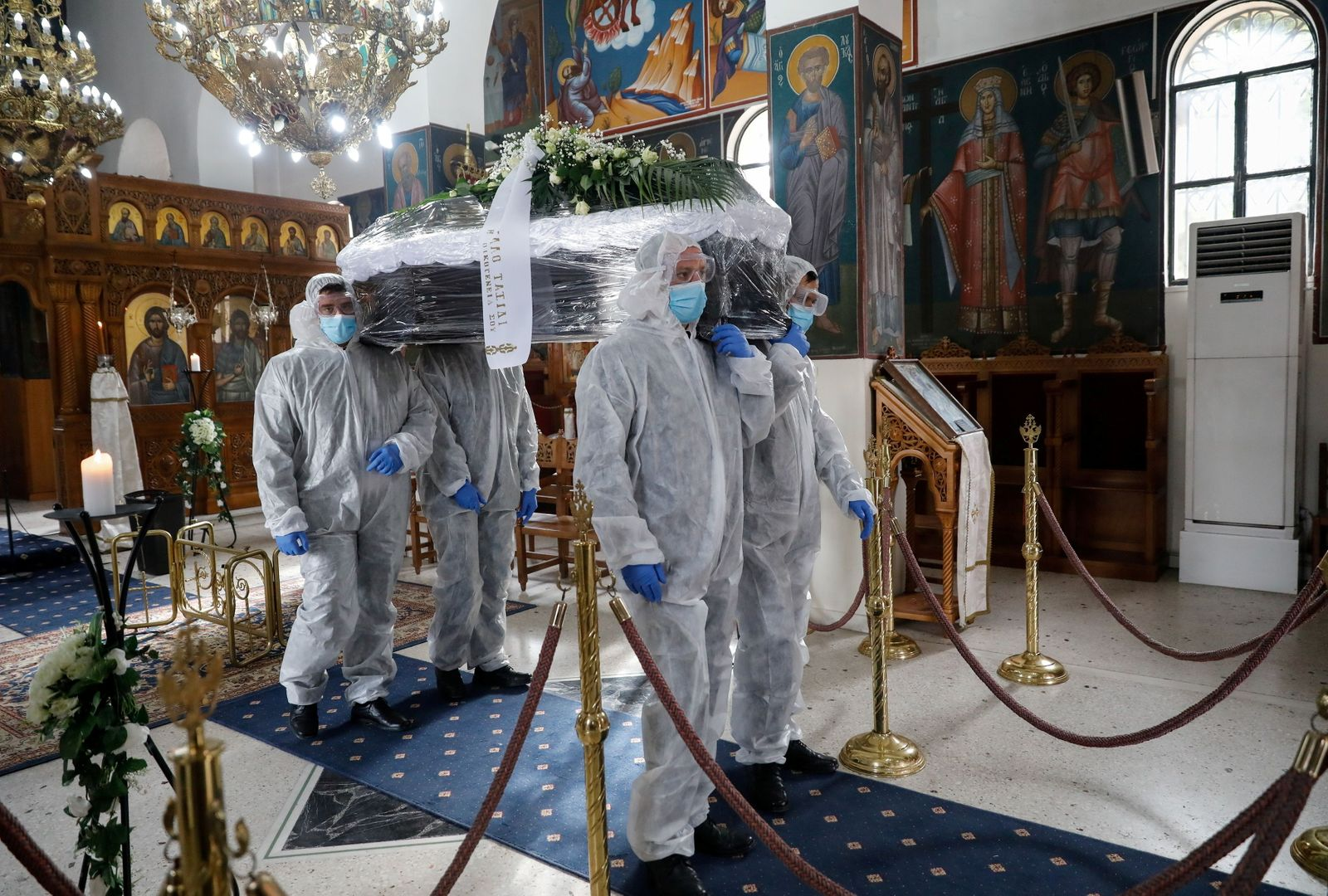 Pallbearers, wearing personal protective equipment (PPE), carry the coffin of a patient who died from the coronavirus disease (COVID-19), inside a church in Athens