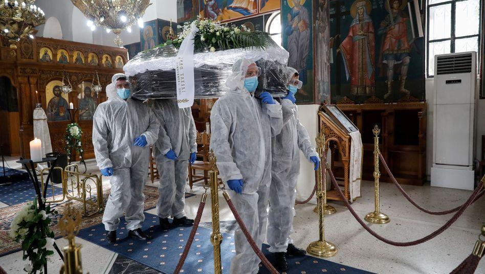 Bestatter mit dem Sarg eines an Covid gestorbenen Griechen in Athen (Dezember 2020): Isoliert bis über den Tod hinaus