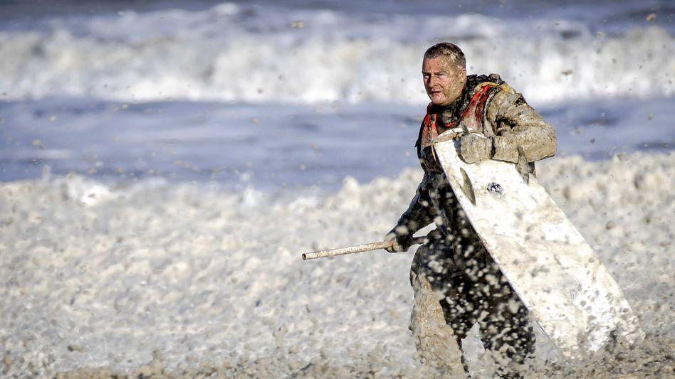 Einsatz in Scheveningen: Eine Rettungskraft bringt ein Surfbrett an Land