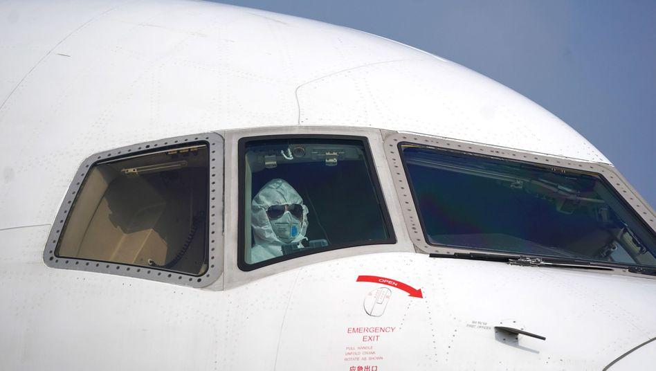Ein Pilot in Schutzanzug parkt ein Flugzeug an der Entladestelle auf dem Internationalen Flughafen Wuhan-Tianhe