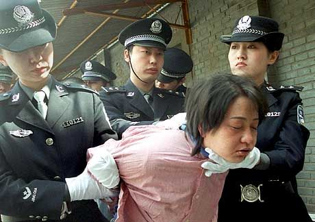 A woman prisoner being taken for her execution after she was sentenced to death at a sentencing rally in Beijing.
