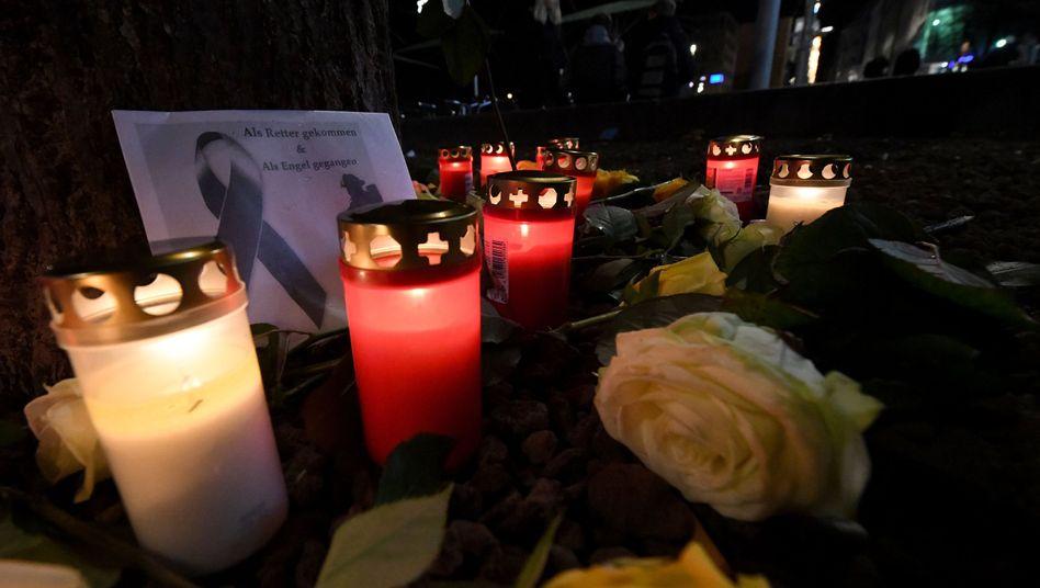 In Augsburg brennen am Königsplatz Kerzen, Menschen haben Blumen niedergelegt. Ein Mann war am Freitagabend in einer Auseinandersetzung mit einer Gruppe so schwer verletzt worden, dass er starb.