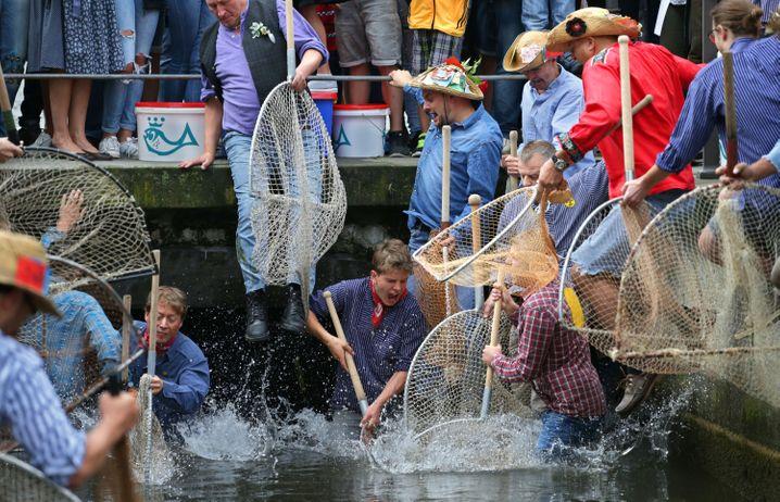 Die Tradition wiegt schwer: Auf einen Böllerschuss hin springen die Fischer ins Wasser