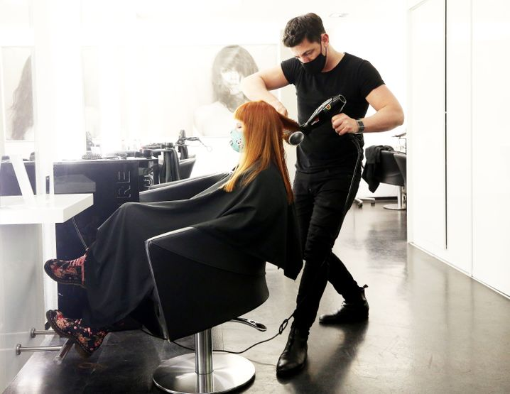 Ein Essener Friseur föhnt eine der letzten Kundinnen vor dem vorläufigen Ladenschluss