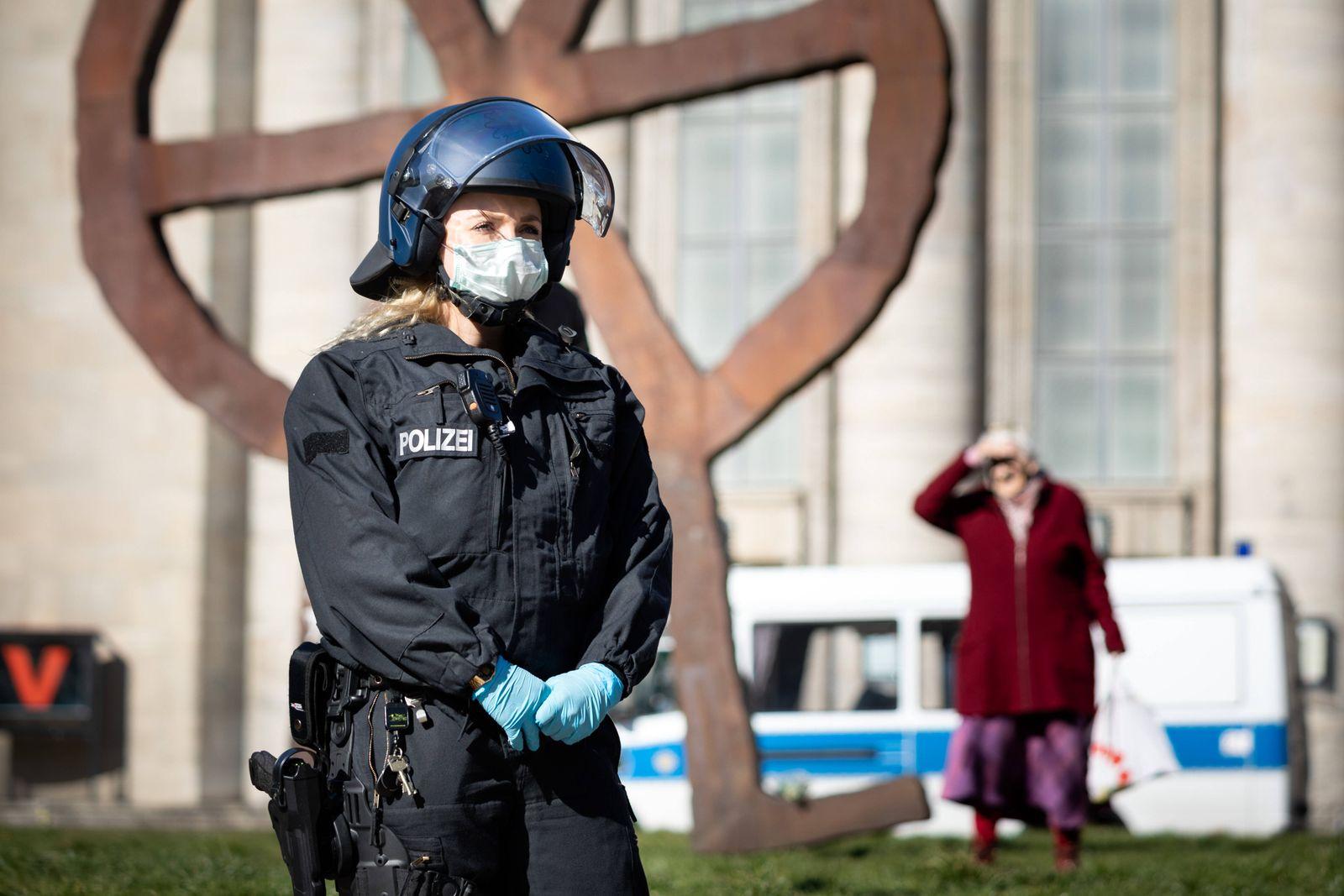 Verschwörungstheoretiker protestieren gg Corona-Einschränkungen Eine Polizistin mit Atemschutzmaske vor der Volksbühne a