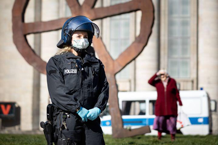 Eine Polizistin mit Atemmaske am Rande einer Demonstration vor der Berliner Volksbühne