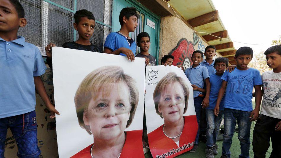 Palästinensische Kinder halten Poster mit Merkel-Porträt