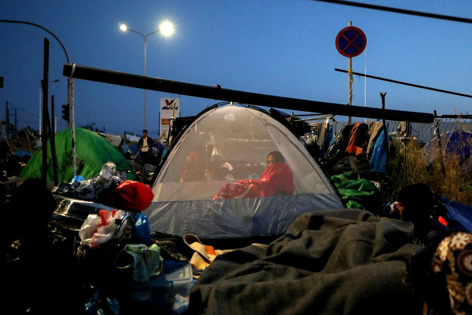 A woman is seen inside a tent as refugees and migrants from the destroyed Moria camp sleep, near a new temporary camp, on the island of Lesbos
