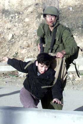 Kontrolle: Ein israelischer Soldat schubst einen palästinensischen Jungen