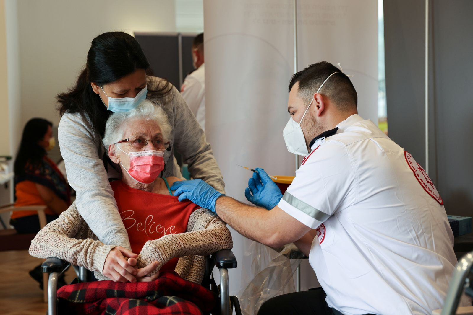 A elderly woman receives a booster shot of her vaccination against the coronavirus disease (COVID-19) at an assisted living facility, in Netanya