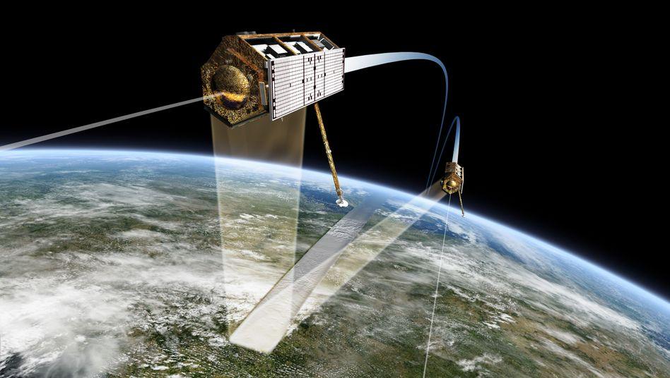 Die Satelliten TanDEM-X und TerraSAR-X fliegen in nördlicher Richtung über Deutschland entlang der Tag-Nacht-Grenze