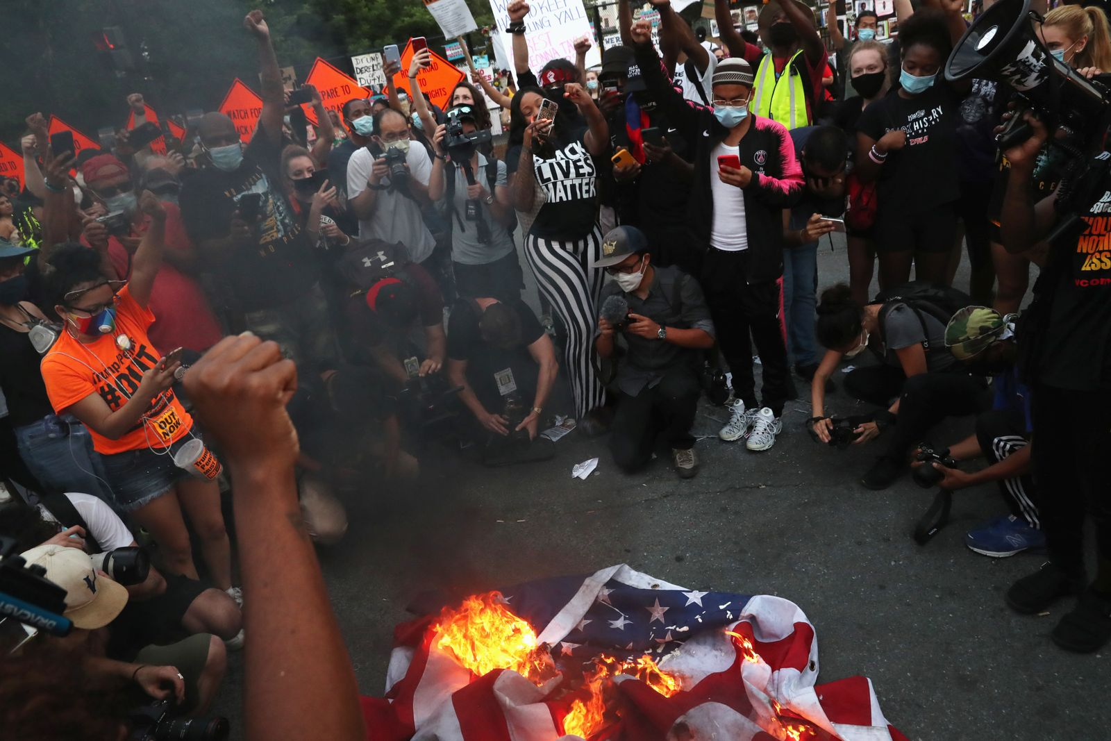 A group of protesters burn an American flag, even as other protesters disagreed with the act, during a protest against racial inequality and police violence near Black Lives Matter Plaza
