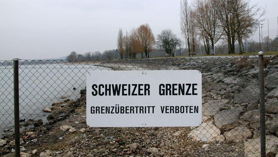 Ein Schild weist am Ufer des Bodensees auf die Grenze zwischen der Schweiz und Deutschland hin (Archivbild)
