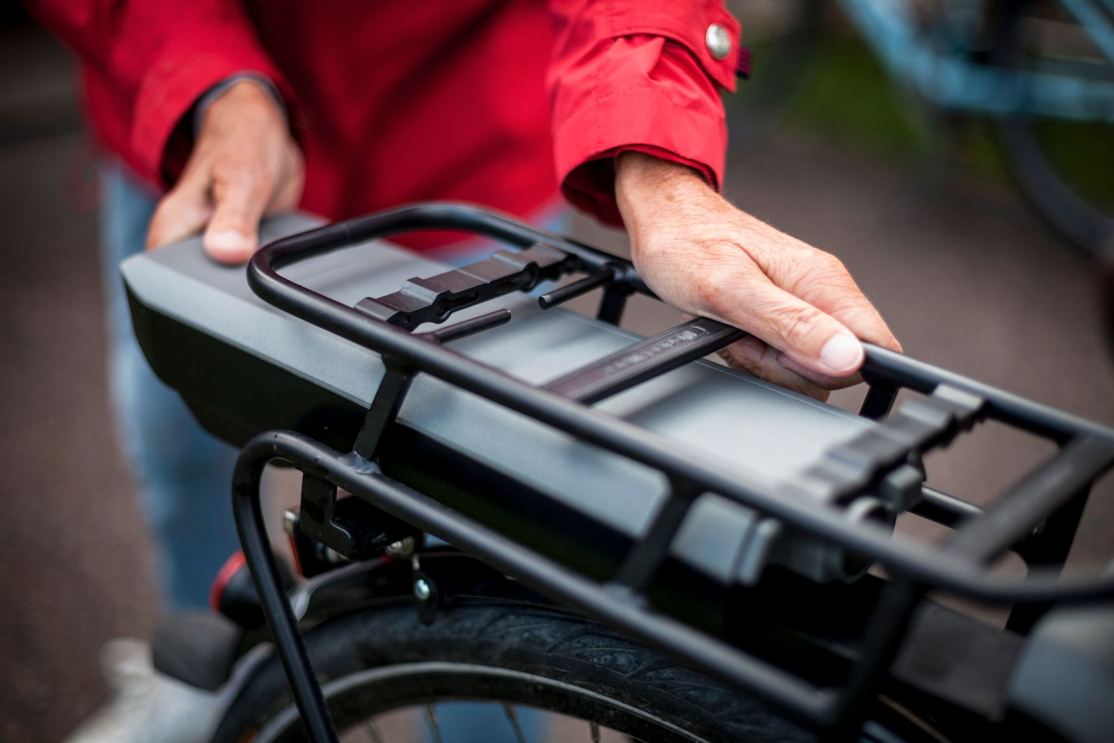 Midsection of senior woman inserting battery in backseat of electric bicycle