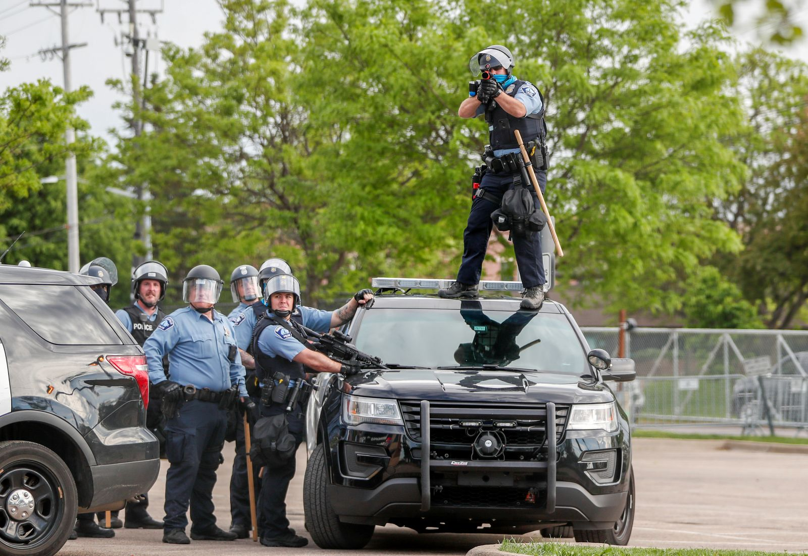Police officer aims gun before firing at people at the Minneapolis Police Department's Third Precinct station to protest the death of George Floyd, in Minneapolis, Minnesota