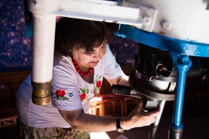 Olga stellt das Okular am Teleskop ein, seit 30 Jahren entdeckt sie so das Weltall