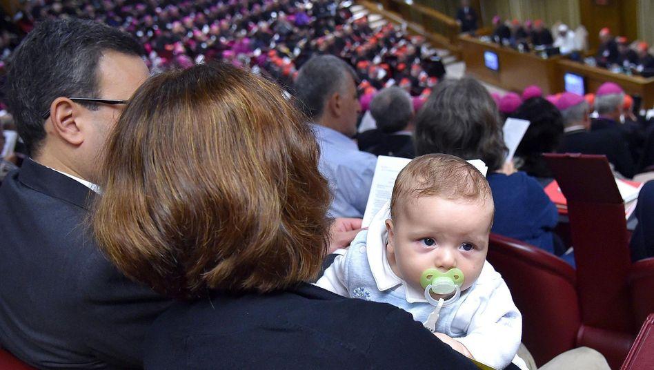 Katholisches Familienidyll: Mann, Frau und Baby sowie zahlreiche Geistliche auf der Familiensynode