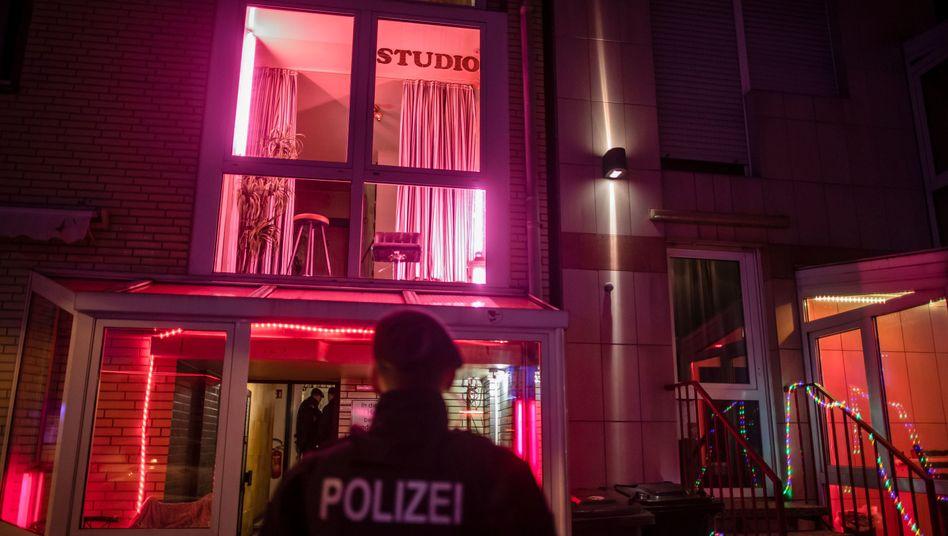 Dunkle Nacht, rotes Licht: Ein Polizist während der Razzia in einem Bordell, die bis zum Samstagmorgen dauerte