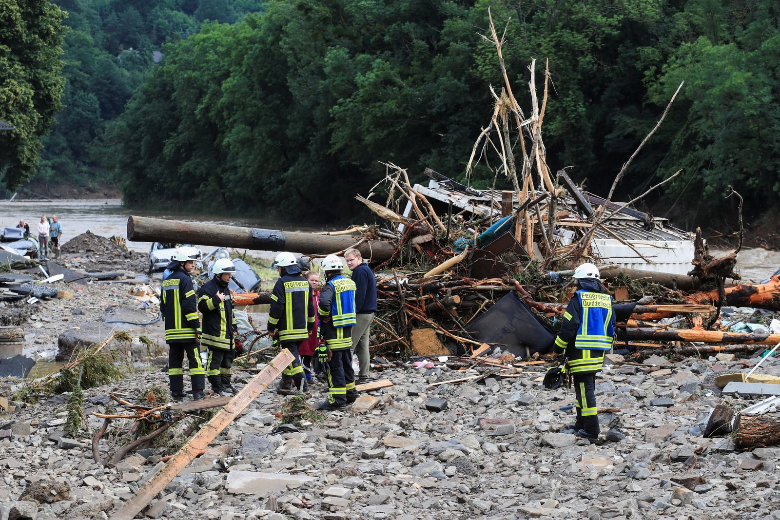 Firefighters speak with people next to debris brought by the flood following heavy rainfalls in Schuld