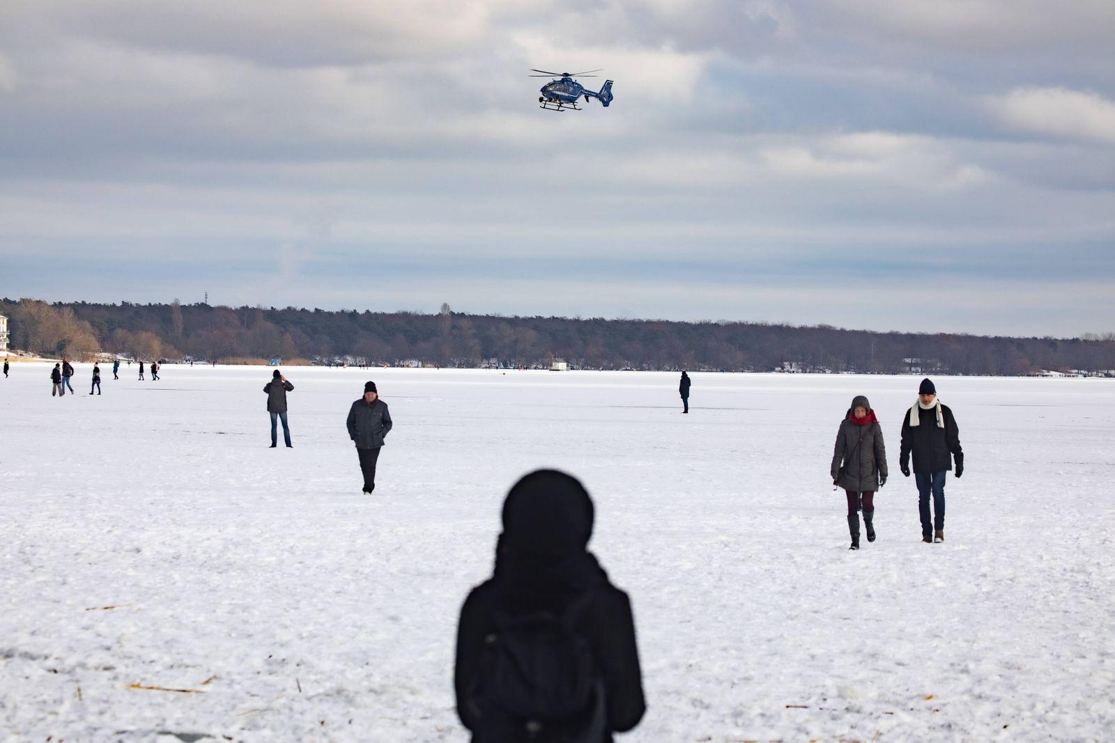 Die Polizei bittet mittels Lautsprecherdurchsagen aus dem Hubschrauber die Menschen, die Eisfläche auf dem Müggelsee zu