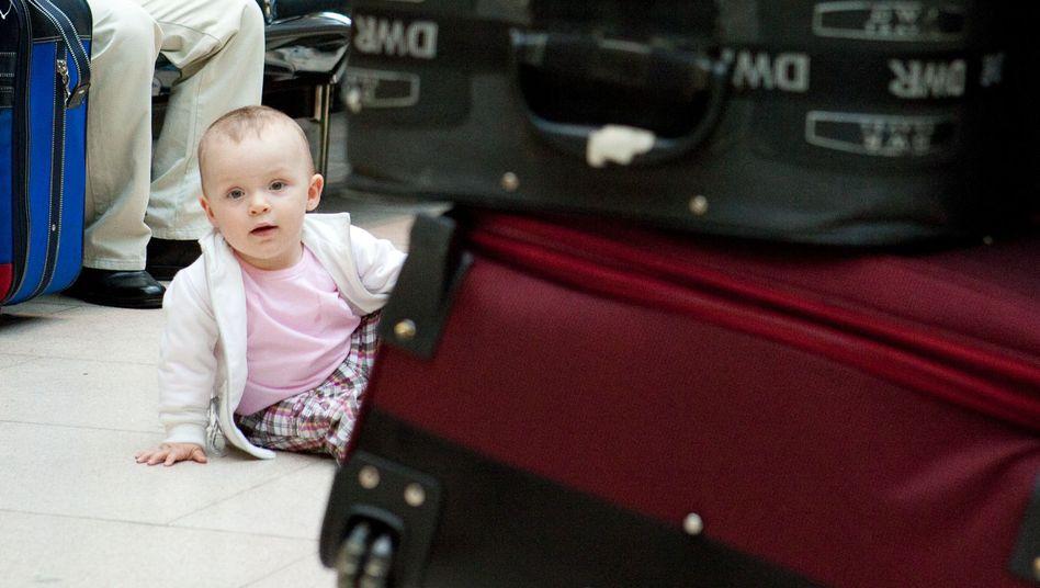 """Kind hinter Koffern: """"Mit drei Monaten zwei Stunden fliegen - das macht gar nichts"""""""