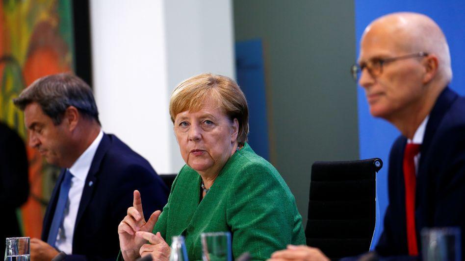 Merkel auf der Pressekonferenz zu den neuen Corona-Maßnahmen mit Bayerns Ministerpräsident Markus Söder (li.) und Hamburgs Erstem Bürgermeister Peter Tschentscher (re.)