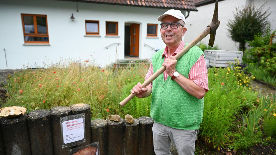 Hansjörg Bayer aus Blaubeuren steht in seinem Garten, wo er den Meteoriten mit dem Pickel herausgehebelt hat