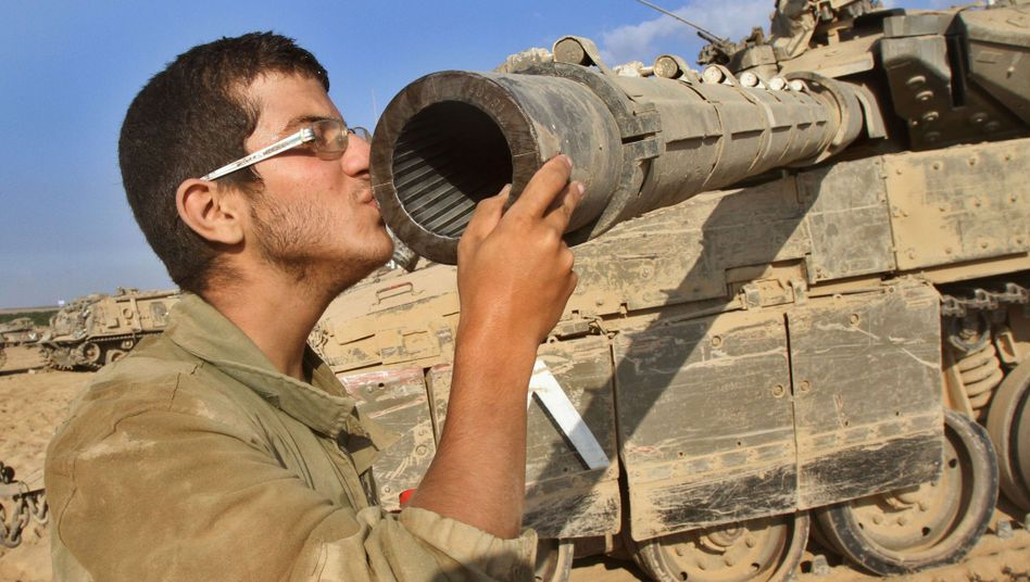Casual attitudes towards weapons: An Israeli soldier kisses his Merkava tank along the border between Israel and the Gaza Strip.
