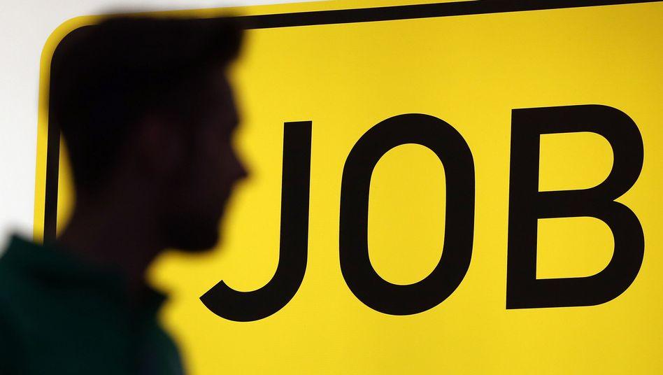 Ein junger Mann vor einem Schild der Arbeitsagentur
