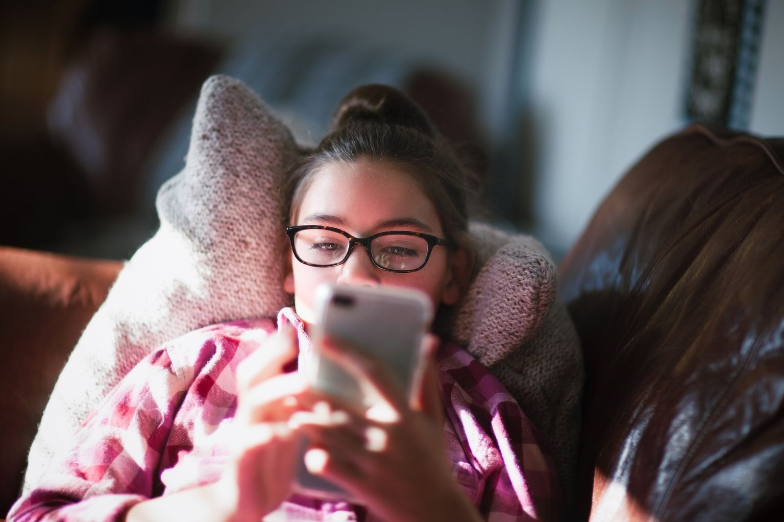 Girl relaxing on sofa, looking at smartphone