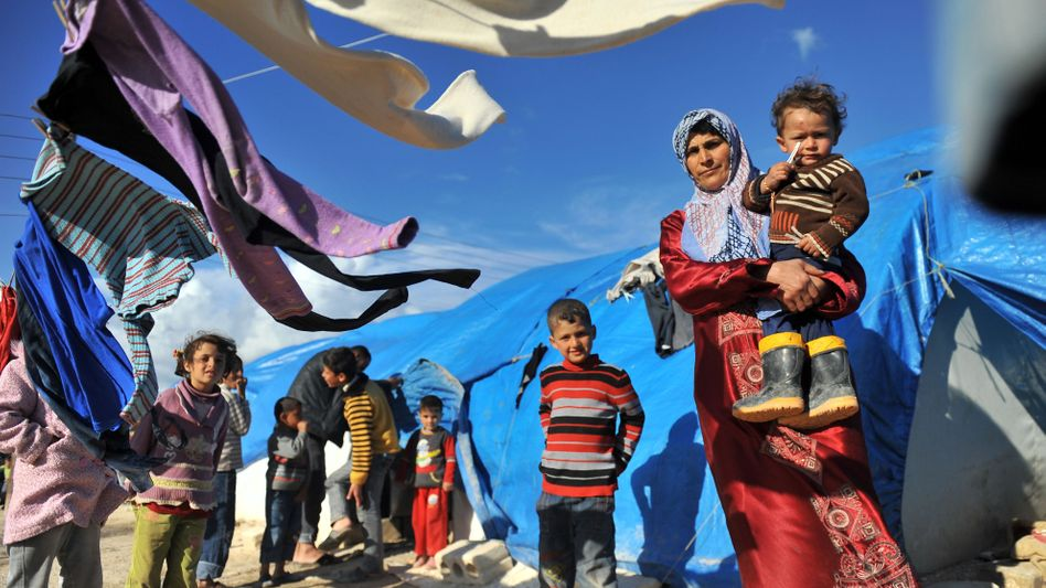 A Syrian woman carries her child in a refugee camp near the Turkish border.