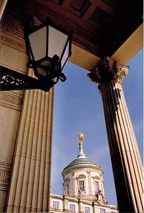 Auf dem Dach des Alten Rathauses trägt Atlas schwer an der Weltkugel