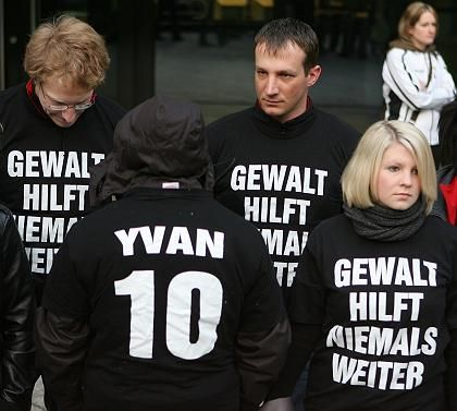 """Freunde des ermordeten Yvan vor dem Landgericht in Stuttgart: Sie tragen T-Shirts mit der Aufschrift """"Gewalt hilft niemals weiter"""" und """"Yvan 10"""" für die Rückennummer, die der ehemalige Handballspieler trug"""