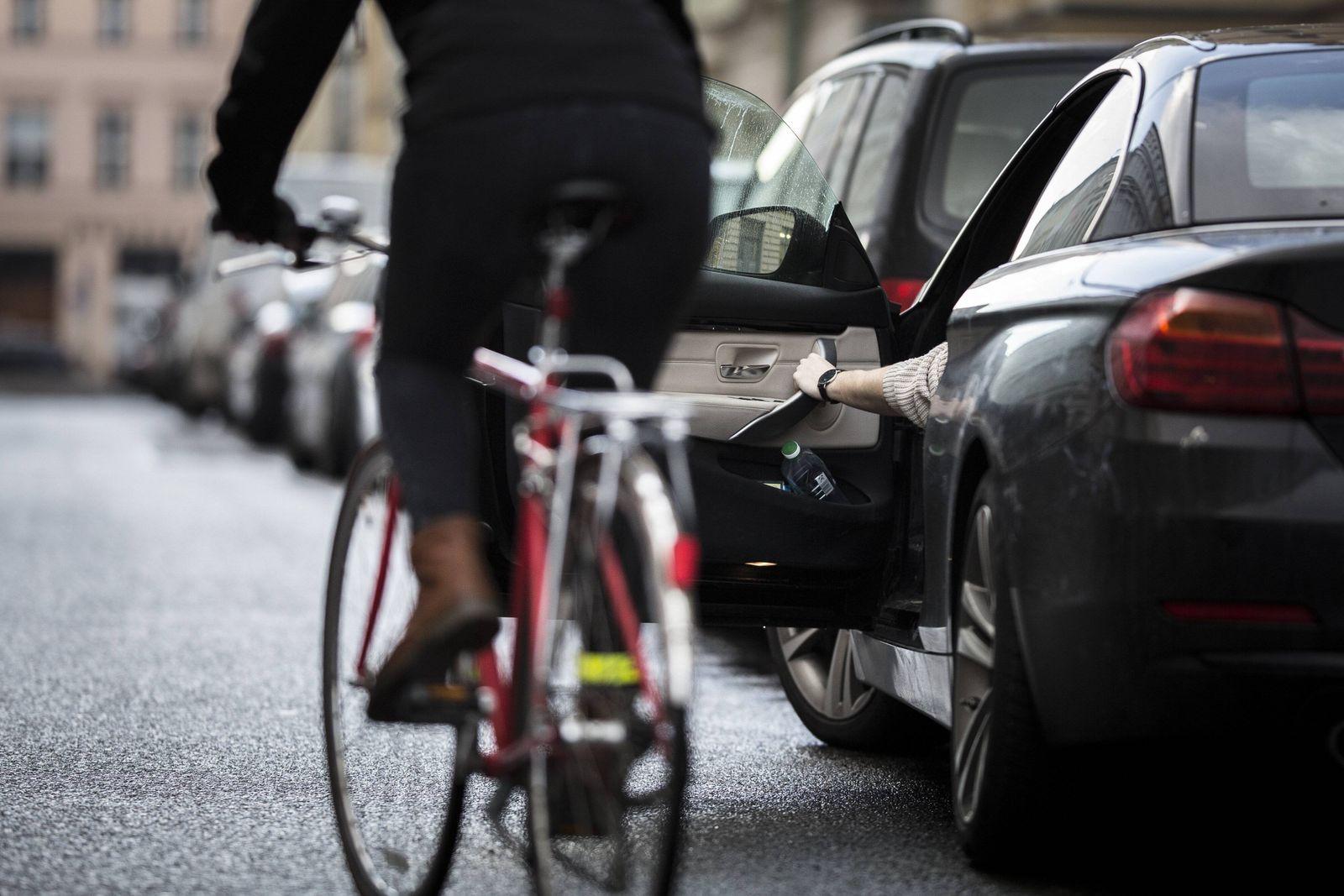 Gestellte Szene zum Thema Verkehrssicherheit Ein Autofahrer oeffnet die Fahrertuer waehrend ein Ra