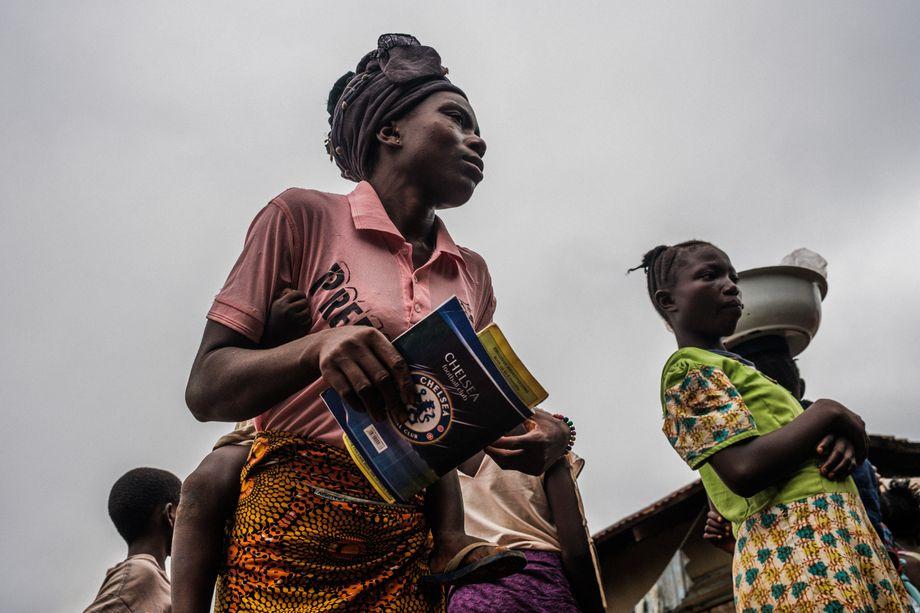 Eine Frau kommt mit ihrem Kind auf dem Rücken und ihrer Patientenakte zur mobilen Klinik von Ärzte ohne Grenzen