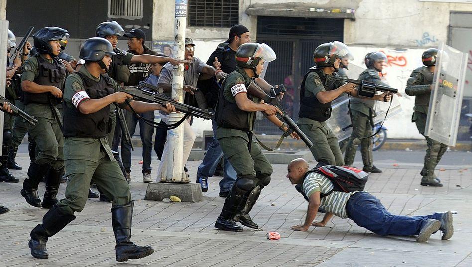 Sicherheitskräfte in Caracas: Ein Demonstrant liegt am Boden