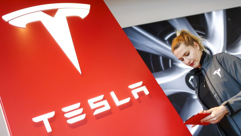 Mitarbeiterin neben Tesla-Logo (Archiv): rote Zahlen trotz höherem Absatz